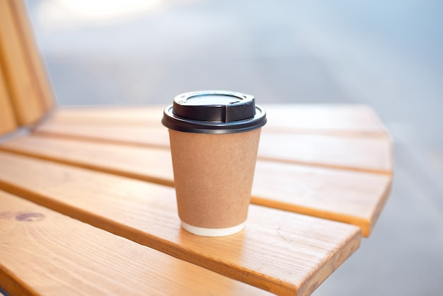 Paper cup of coffee or tea on wooden table on street food festival.