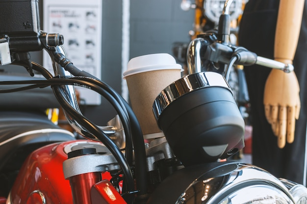 Paper cup of coffee on vintage motorcycle in moto lifestyle cafe and showroom