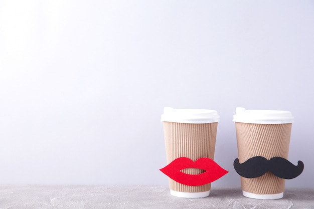 Paper cup of coffee with lips and mustache decoration on grey . valentine's day and wedding concept.