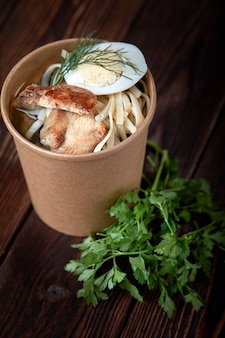 Paper cup noodles with chicken and eggs on wooden background with herbs