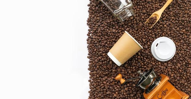 Кофе и фасоль oaf бумажного стаканчика на белой предпосылке таблицы. вид сверху
