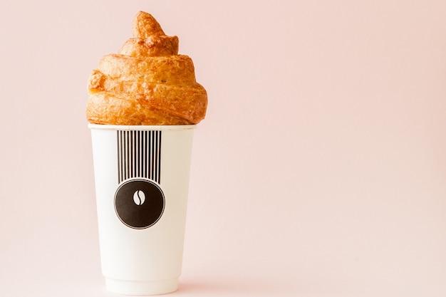 ピンクのコーヒーとクロワッサンの紙コップ