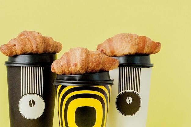 黄色のコーヒーとクロワッサンの紙コップ。