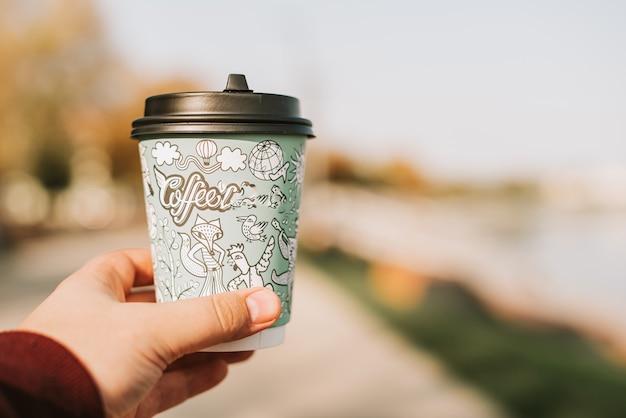 手のクローズアップでコーヒーの紙コップ