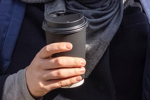 手にコーヒーの紙コップ。手にコーヒーの黒い紙コップ。