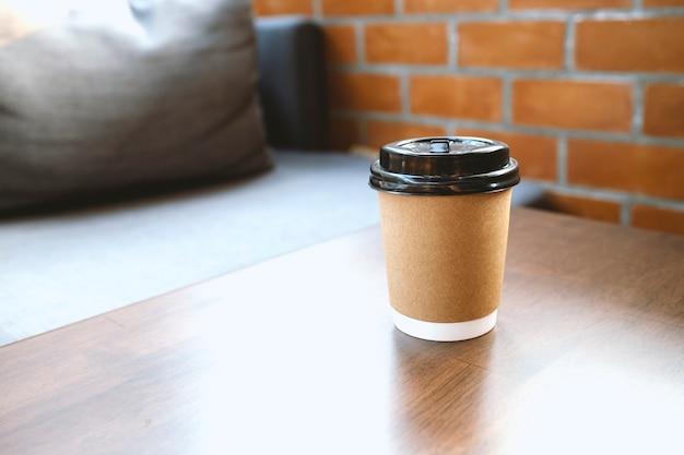 Бумажный стаканчик кофе на столе в кафе