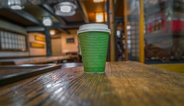 木製の背景にコーヒーの紙コップ