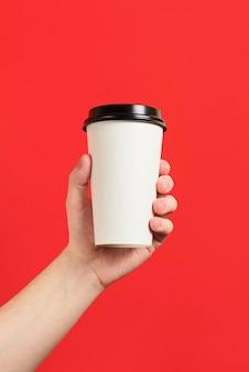 빨간색 배경에 커피 또는 홍차의 종이 컵 절연 종이 컵을 들고 남성 손의 모형 빈 폴리스티렌 커피 잔의 전면보기 모형