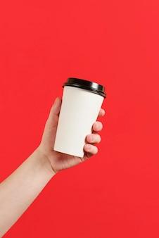 빨간색 배경에 커피 또는 홍차의 종이 컵 절연 종이 컵을 들고 남성 손의 모형