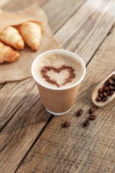 ハート型のコーヒーの紙コップ、クリーム、泡、荒布でクロワッサンの束、古い木製のテーブルでスプーンで乾燥したローストコーヒー豆
