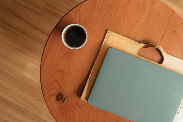 Бумажный стаканчик горячего напитка и ноутбук на столе. концепция работы из дома.