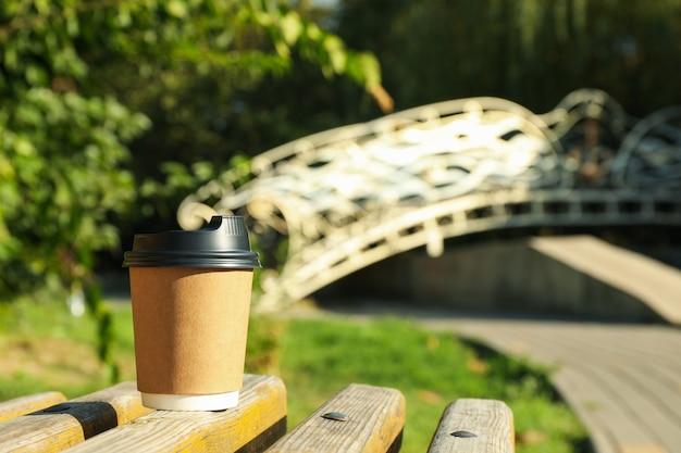 美しい都市公園のベンチに紙コップ