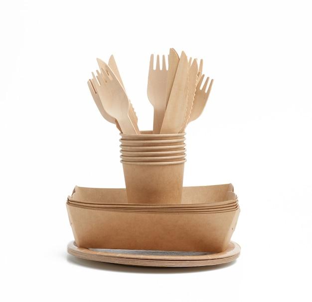 Бумажный стаканчик, тарелки из коричневой крафт-бумаги и деревянные вилки и ножи
