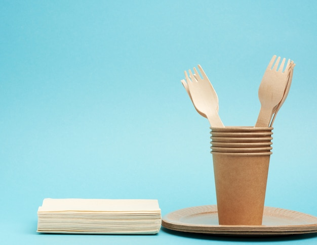 Paper cup,  plates from brown craft paper and wooden forks and knives on a blue background