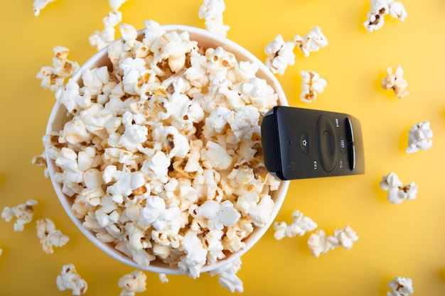Paper cup of popcorn, tv remote, top view. watching cinema