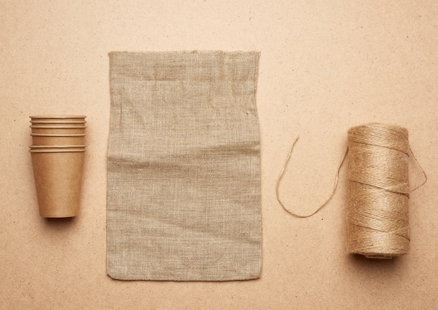Paper cup, skein with brown rope and empty bag on a brown wooden background
