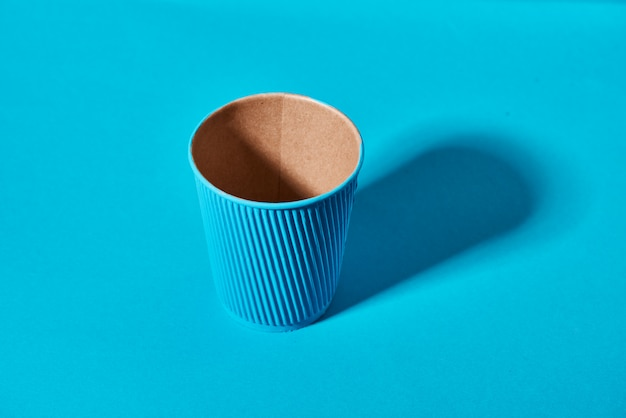 Paper cup standing on solid colored
