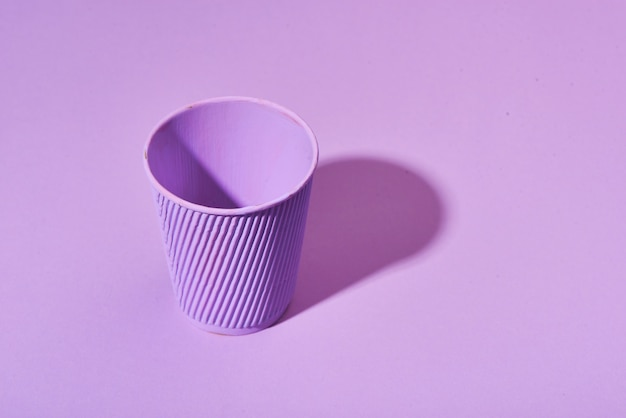 Paper cup standing on solid pink