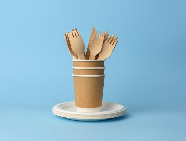 Бумажный стаканчик, белые тарелки и деревянные вилки и ножи на синем фоне. концепция отказа от пластика, нулевые отходы