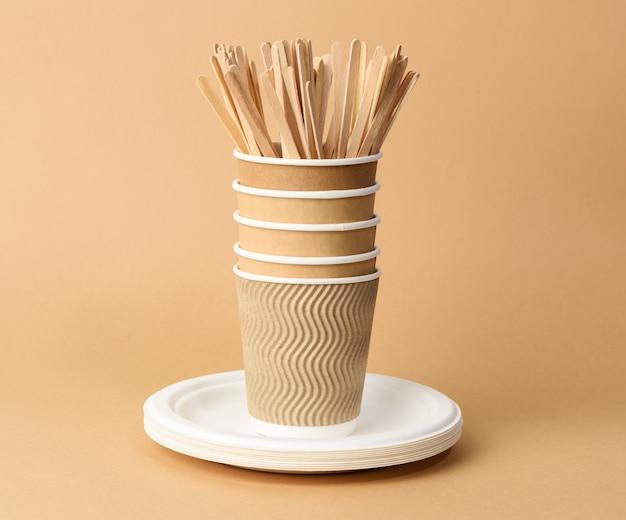 Бумажный стаканчик, белые тарелки и деревянные вилки и ножи на коричневом фоне. концепция отказа от пластика, нулевые отходы
