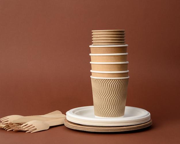 Бумажный стаканчик, белые тарелки и деревянные вилки и ножи на коричневой поверхности. концепция отказа от пластика, нулевые отходы