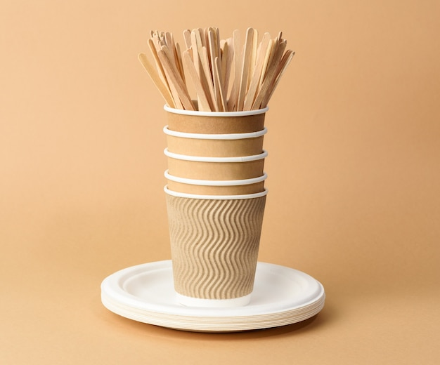 Paper cup, white plates and wooden forks and knives on a brown background. plastic rejection concept, zero waste