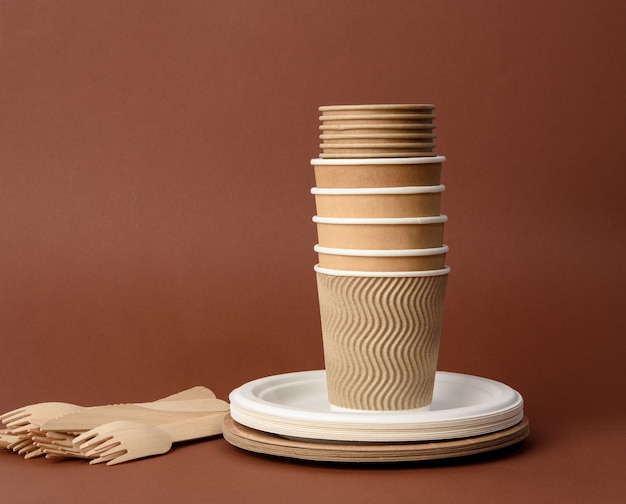 Paper cup, white plates and wooden forks and knives on a brown surface. plastic rejection concept, zero waste