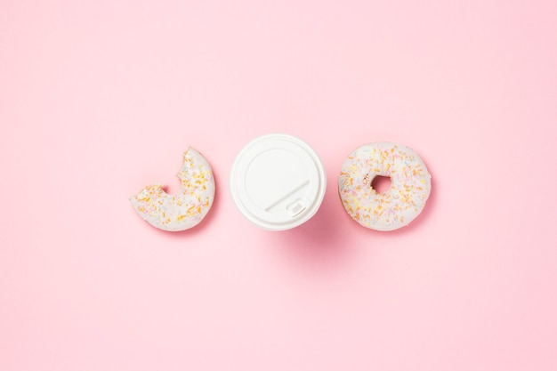 Бумажный стаканчик с пластиковой крышкой, кофе или чай, свежий вкусный сладкий пончик на розовом фоне. концепция быстрого питания, пекарня, завтрак, сладости, кафе, еда на вынос. копировать пространство. плоская планировка, вид сверху.