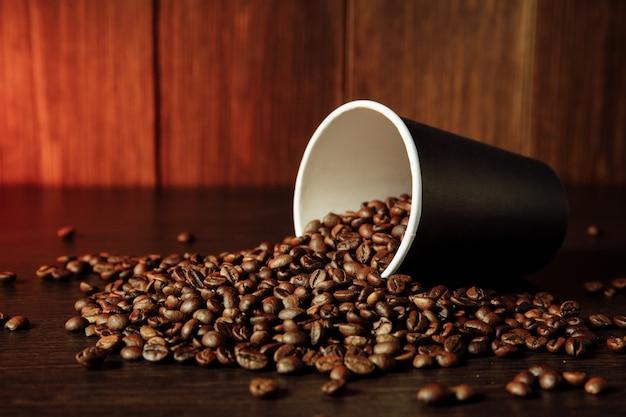 Бумажный стаканчик с ароматными кофейными зернами на деревянном столе.