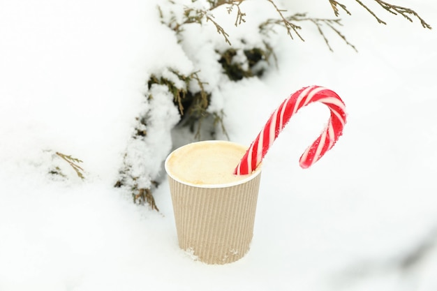 Paper cup with coffee and candy cane outdoor in winter