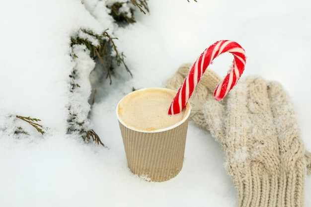 Paper cup with coffee and candy canes and mittens outdoor in winter