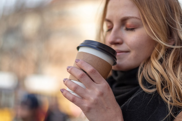 Paper cup with coffee in girl's hands on natural morning background