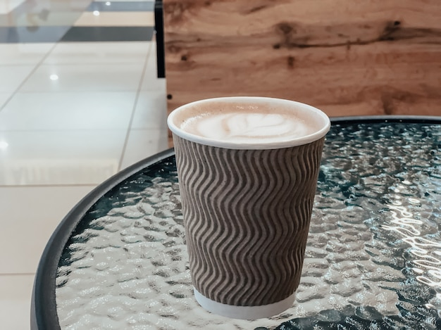 Paper cup with coffee on a glass table in a cafe. place for text.