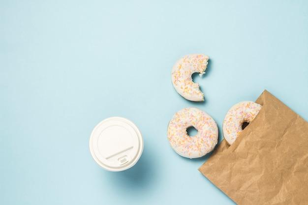 Бумажный стаканчик с кофе или чаем и бумажный мешок с свежие вкусные сладкие пончики на синем фоне. концепция быстрого питания, пекарня, завтрак, сладости. минимализм. плоская планировка, вид сверху.