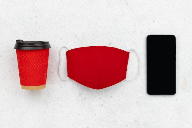 Paper cup with face mask and smartphone on gray table. flat lay top view new normal autumn winter composition.