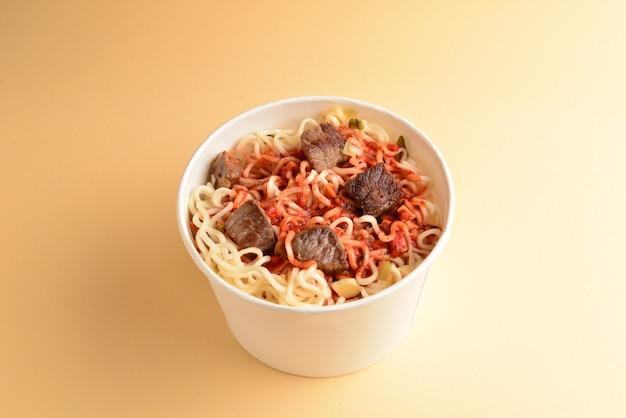 Бумажный стаканчик с лапшой рамен быстрого приготовления с говядиной и овощами.