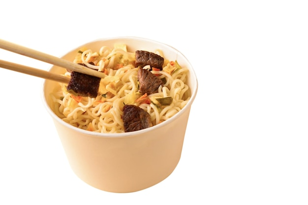 Paper cup with instant ramen noodles with beef and vegetables isolated on white background.