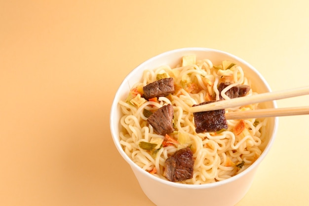 Paper cup with instant ramen noodles with beef and vegetables.