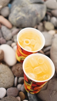 돌, 자갈 해변의 배경에 레모네이드와 종이 컵. 해변 휴가 개념