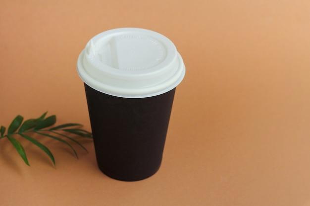 茶色の壁にあなたと一緒にコーヒーやホットドリンク用の蓋付きの紙コップ。