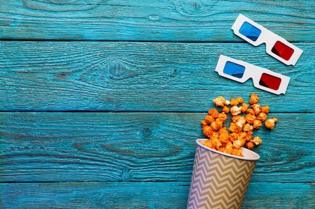 파란색 배경에 팝콘과 3d 안경이 있는 종이 컵. 평면도.
