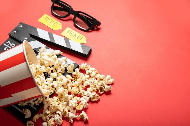 赤い背景の上のポップコーンと映画のクラッパーボードと紙コップ。テキストのための場所