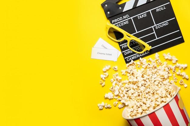 テキストのための場所、黄色の背景にポップコーンと映画のクラッパーと紙コップ