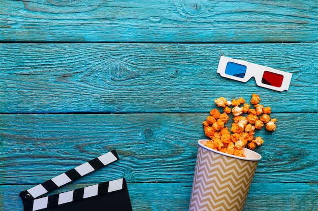 Paper cup with popcorn over blue old wooden table