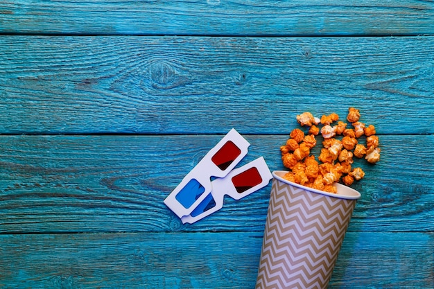 Paper cup with popcorn and d glasses on blue background top view