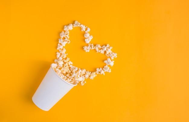 黄色の背景にハートの形をしたポップコーンと紙コップ。フラットレイバナー、上面図。映画のコンセプトに行きます。私は映画を見るのが好きです。