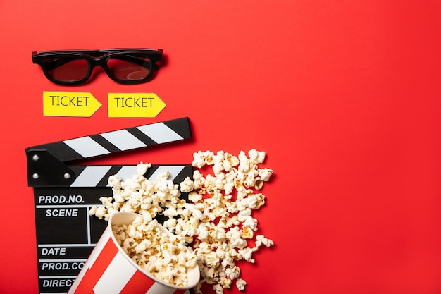 Paper cup with popcorn and movie clapper board on a red background. place for text