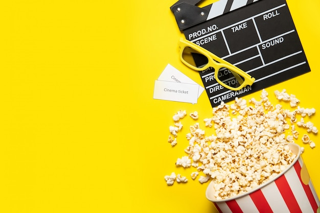 Paper cup with popcorn and movie clapper on a yellow background, place for text