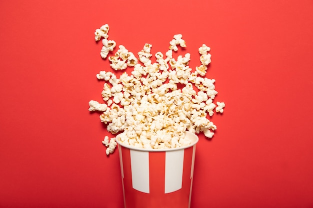 Paper cup with popcorn on a red background