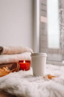窓辺にお茶の入った紙コップ。秋の気分。